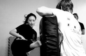 Kvinna sparkar mot mitts, Krav Maga, självförsvarsakademin